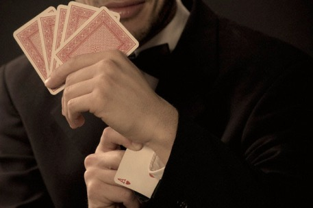 Man holding playing cards, ace in sleeve
