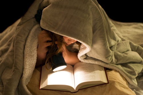 A young girl reading a book under the covers with a flashlight; Shutterstock ID 25849123; PO: The Huffington Post; Job: The Huffington Post; Client: The Huffington Post; Other: The Huffington Post